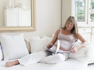 Pregnant-woman-reclining-on-sofa-with-book