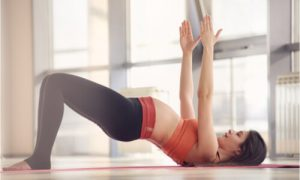 The pregnant woman exercises her back to alleviate the back pain.