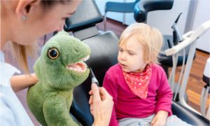 A female dentist using a stuffed toy to show the child how she will help clean teeth.