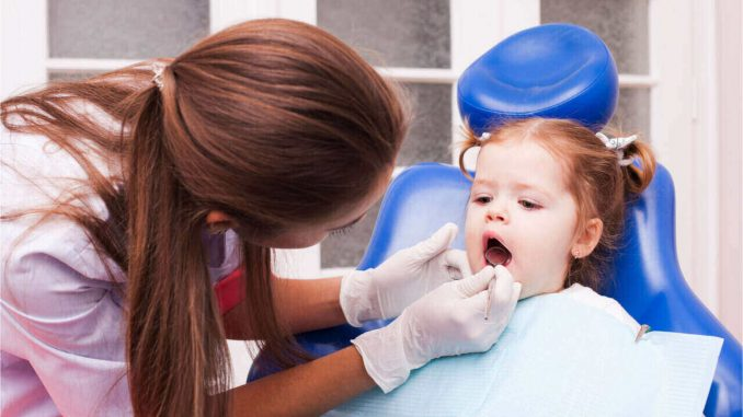 A female dentist attending the baby's first dental appointment.